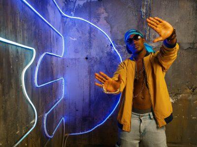 Black rapper in underpass neon light on background